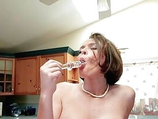 Hot Cougar Krissy Lynn Uses A Large Glass Fake Penis In The Kitchen